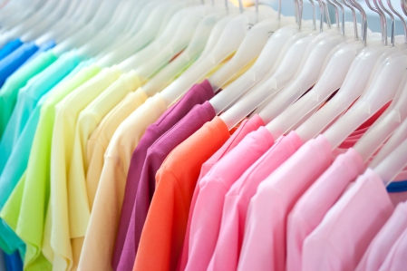 A row of colorful row t-shirts hanging on hangers