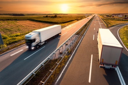 Two trucks on highway in motion blur at sunset